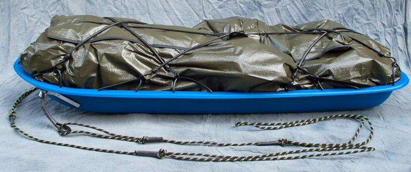 Pulk with load wrapped in a tarp